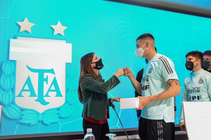The Secretary of Sports handing over the Argentine flag to each of the footballers.