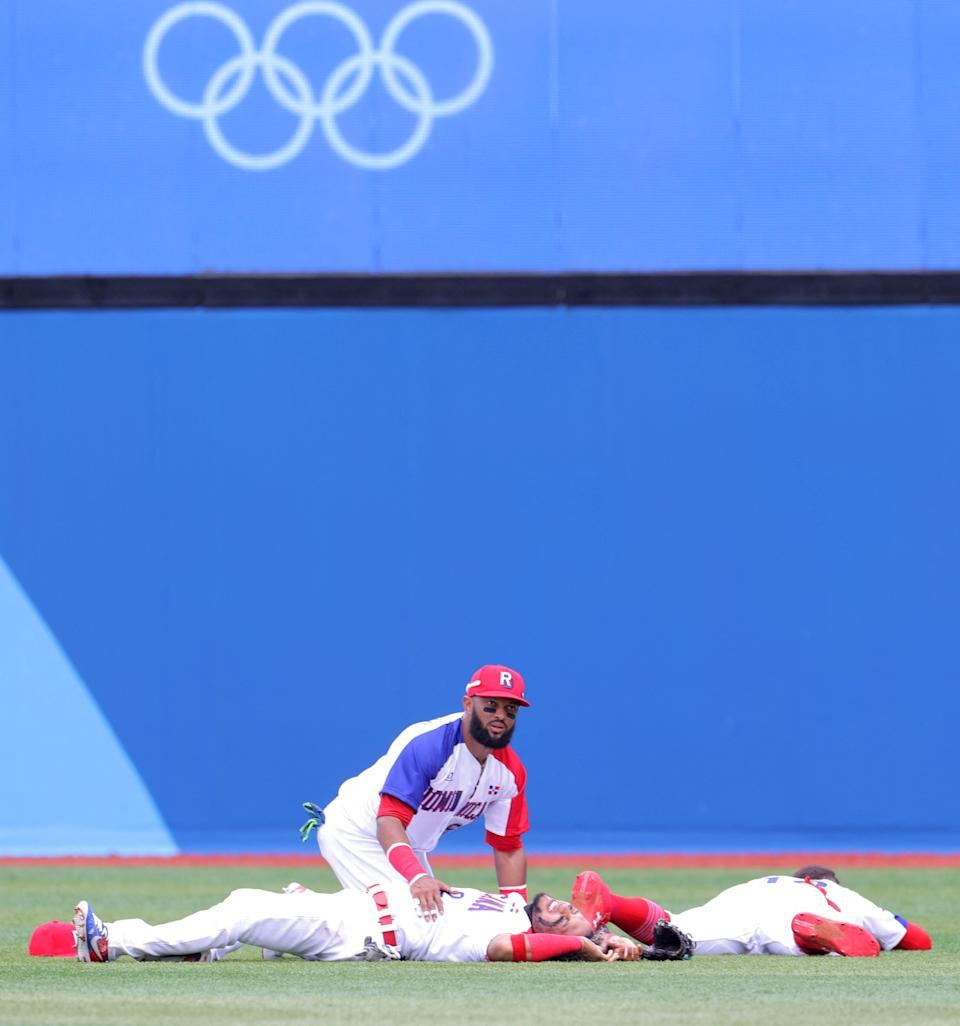 Dominican Republic & # 39; s center fielder Emilio Bonifacio (C) comforts second baseman Gustavo Nunez (bottom L) after collided with right fielder Julio Rodriguez (bottom R) while catching a pop fly by Mexico & # 39; s Ramiro Pena (not in photo ) during the third inning of the Tokyo 2020 Olympic Games baseball opening round group A game between Mexico and Dominican Republic at Yokohama Baseball Stadium in Yokohama, Japan, on July 30, 2021. (Photo by KAZUHIRO FUJIHARA / AFP) (Photo by KAZUHIRO FUJIHARA / AFP via Getty Images)