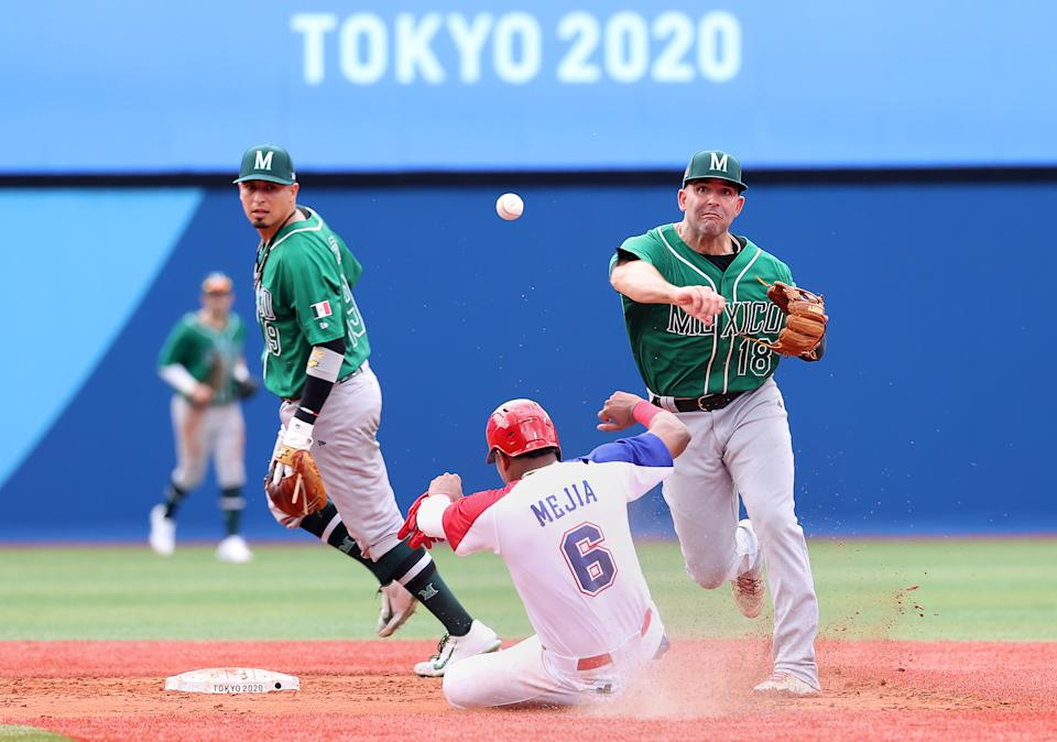 YOKOHAMA, JAPAN - JULY 30: Daniel Espinosa # 18 of Team Mexico throws to first base to finish the double play as Erick Mejia Buret # 6 of Team Dominican Republic slides into second base too late in the sixth inning during the baseball opening round Group A game on day seven of the Tokyo 2020 Olympic Games at Yokohama Baseball Stadium on July 30, 2021 in Yokohama, Kanagawa, Japan. (Photo by Koji Watanabe / Getty Images)