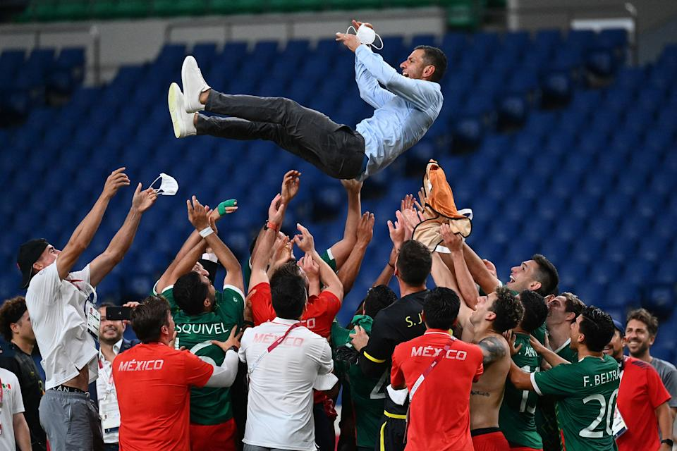Mexico & # 39; s players throw Mexico & # 39; s coach Jaime Lozano into the air as they celebrate winning the Tokyo 2020 Olympic Games men & # 39; s bronze medal football match between Mexico and Japan at Saitama Stadium in Saitama on August 6, 2021 (Photo by Vincenzo PINTO / AFP) (Photo by VINCENZO PINTO / AFP via Getty Images)